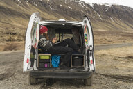 Iceland, man sitting in van using smartphone and laptop - AFVF00505