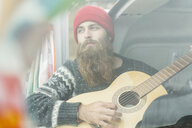 Portrait of hipster in van playing guitar - AFVF00508