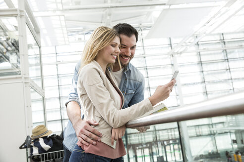 Young couple looking at smartphone in airport departure lounge - CUF12069