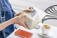 Hand of mature woman removing euro note from purse at sidewalk cafe, Fiesole, Tuscany, Italy - CUF12072