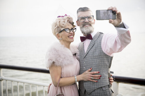 1950's vintage style couple taking smartphone selfie on pier - CUF12183