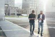 Two young male hipsters walking in city while looking at smartphones - CUF12195