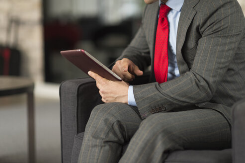 Neck down view of businessman sitting in office using digital tablet - CUF12291