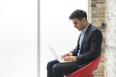 Businessman sitting on office chair typing on laptop - CUF12300