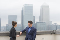 Businessman and female colleague meeting on city office roof terrace, London, UK - CUF12312