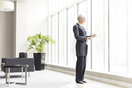 Mature businesswoman looking at smartphone by office window - CUF12315