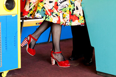 Woman in red shoes in amusement arcade, Bournemouth, England - CUF12363