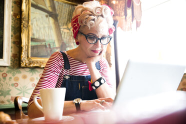 Quirky woman using laptop in bar and restaurant, Bournemouth, England - CUF12366