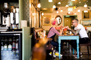 Quirky couple relaxing in bar and restaurant, Bournemouth, England - CUF12369