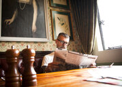 Quirky man reading newspapers in bar and restaurant, Bournemouth, England - CUF12378