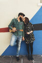 Cool couple leaning against abstract wall gazing at each other - CUF12405