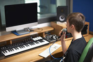 Young male college student talking into microphone in recording studio - CUF12432