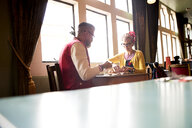Quirky couple relaxing in bar and restaurant, Bournemouth, England - CUF12438