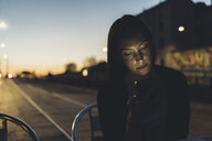 Young woman on street looking at smartphone at dusk - CUF12450