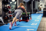 Rear view of young woman training, pushing weight sled in gym - CUF12501