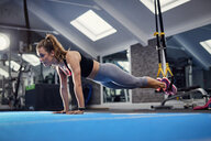 Young woman doing push ups using exercise handles in gym - CUF12513