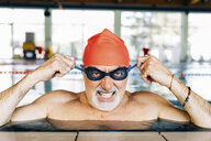 Senior man pulling mean face wearing goggles in swimming pool - CUF12615