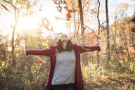 Young woman throwing autumn leaves in forest - ISF02102