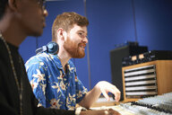 Two young male college students at sound mixer in recording studio - CUF12826