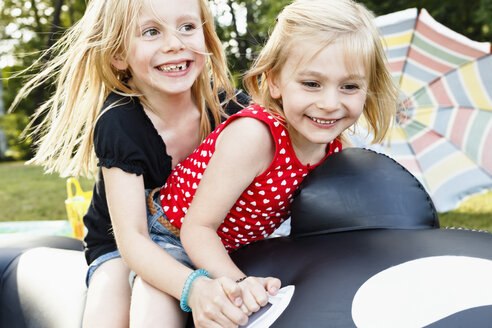 Two young sisters sitting on inflatable whale in park - CUF12988