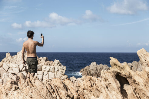 Rear view of young man on rock using smartphone to take photograph of horizon over ocean, Costa Paradiso, Sardinia, Italy - CUF13018