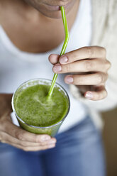 Woman drinking green smoothie with straw - CUF13111
