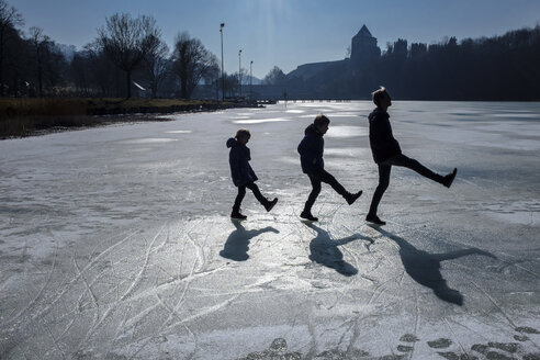 Three children playing on icy surface - HAMF00323