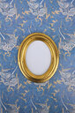 Oval golden picture frame on wallpaper with Art Nouveau floral design - AXF00805