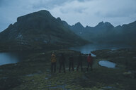 Norway, Lofoten, Moskensoy, Five young man looking at Agvatnet lake at dawn - GUSF00770