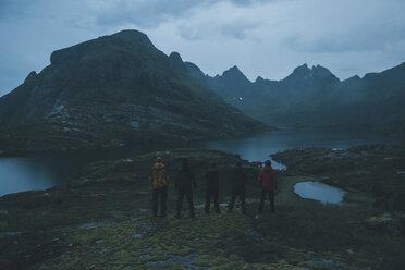 Norway, Lofoten, Moskensoy, Five young man looking at Agvatnet lake at dawn - GUSF00770
