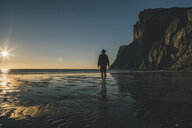 Norway, Lofoten, Moskenesoy, Man walking into the sunset at Kvalvika Beach - GUSF00794
