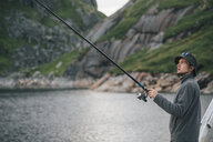 Norway, Lofoten, Moskenesoy, Young man fishing at Krokvatnet - GUSF00815