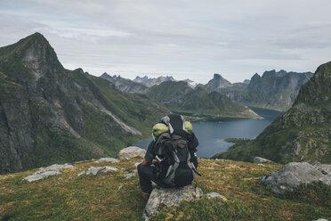 Norway, Lofoten, Moskenesoy,  Man sitting on a rock, looking over Kjerkefjord - GUSF00818