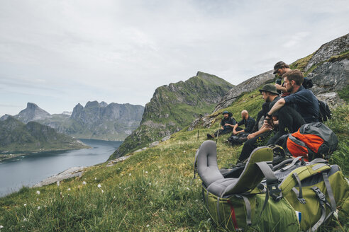 Norway, Lofoten, Moskenesoy, Group of young men sitting on grass, looking over Kjerkefjord - GUSF00821