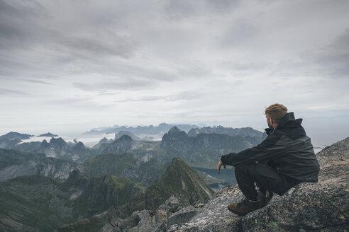 Norway, Lofoten, Moskenesoy, Young man sitting at Hermannsdalstinden, looking over Kjerkefjord - GUSF00827