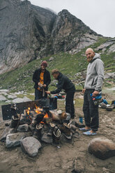 Norway, Lofoten, Moskenesoy, Young men starting a camp fire at Bunes Beach - GUSF00848