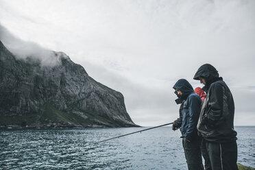 Norway, Lofoten, Moskenesoy, Young men fishing at Horseid Beach - GUSF00863
