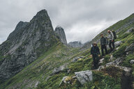 Norway, Lofoten, Moskenesoy, Young men hiking at Markan mountain - GUSF00869