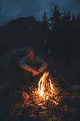 Norway, Lofoten, Moskenesoy, Young man sitting at camp fire - GUSF00872