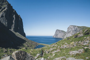 Norway, Lofoten, Moskenesoy, Young man hiking at Kvalvika Beach - GUSF00881