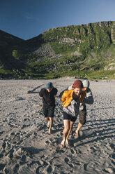 Norway, Lofoten, Moskenesoy, Group of young men preparing camp at Kvalvika Beach - GUSF00890