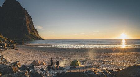 Norway, Lofoten, Moskenesoy, Group of young men camping at Kvalvika Beach - GUSF00893