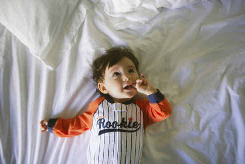Portrait of baby girl wearing jumpsuit lying on bed - GEMF01994