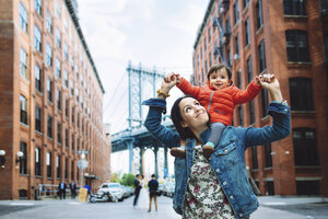 USA, New York, New York City, Mother and baby in Brooklyn with Manhattan Bridge in the background - GEMF02000