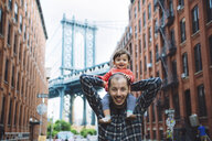 USA, New York, New York City, Father with a baby on shoulders in Brooklyn with Manhattan Bridge in the background - GEMF02003