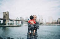 USA, New York, New York City, Father hugging a baby in Brooklyn with Brooklyn Bridge and Manhattan in the background - GEMF02006