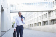 Businessman with laptop bag walking at courtyard of modern office buildings - DIGF04318