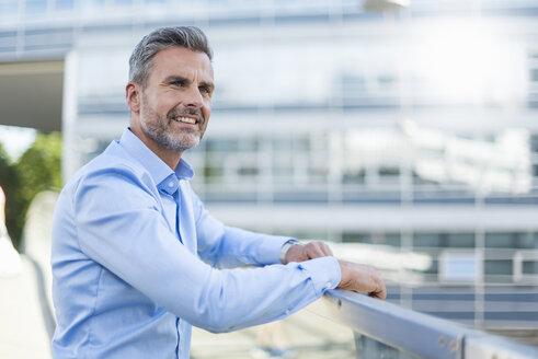 Portrait of smiling businessman wearing light blue shirt - DIGF04330