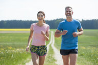 Couple running on field path - DIGF04348