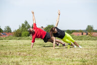 Couple doing side plank exercise on meadow - DIGF04354